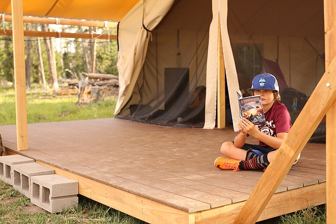 Dylan Gormley reads a book outside of a raised platform tent at BookTrails new overnight camp location last July.