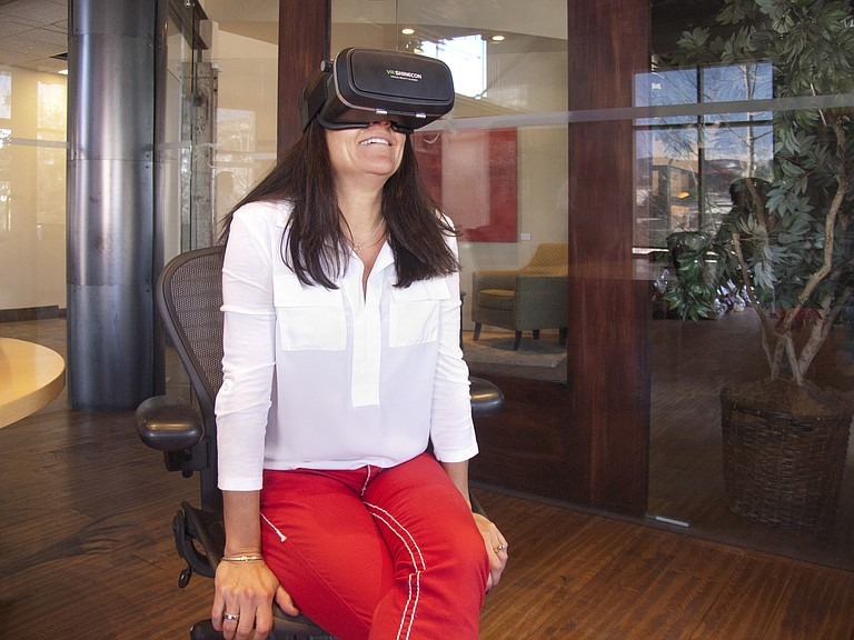 Broker Cheryl Foote views a virtual tour of her 3012 Aspen Leaf Way listing through virtual reality goggles.