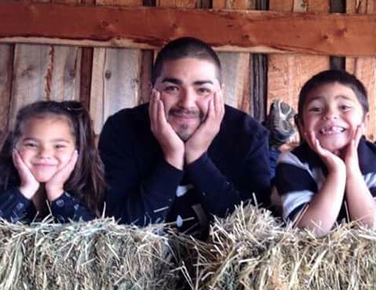 Jesse James Romero, center, poses with 8-year-old daughter Serina, left, and 9-year-old son, Zachary.