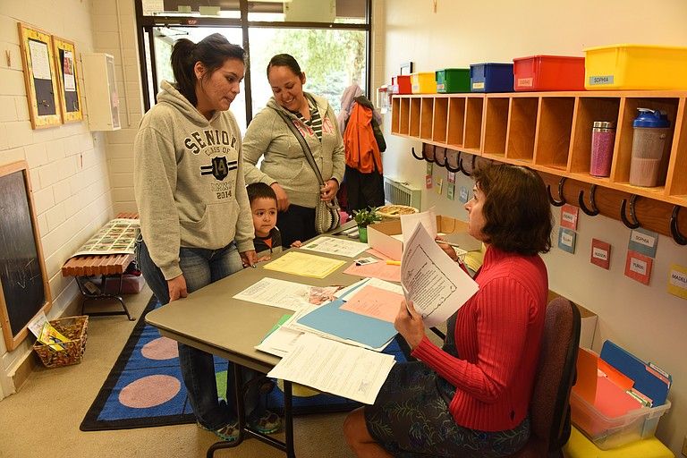 Michelle Gutierrez, left, Adan Barragan and Olga Mora get Adam registered for his first day of classes at the Early Childhood Center in 2015.