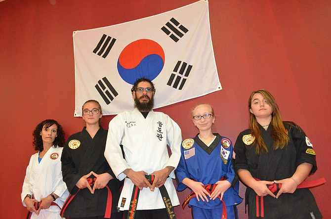Taekwondo instructor Paul Cruz, center, gathers with red belt students Shasta Hyer, Hannah Germond, Ashley Smith and Brooke Germond in the studio of Northwest Colorado Tae Kwon Do/Hapkido. Students recently competed in the Montrose Spring Karate Tournament, amid many different martial arts styles.