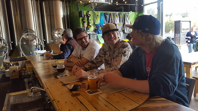 Colin Biafore, Reed Hines and Barrett Sharp enjoy a beer during Token Tuesdays at Mountain Tap Brewery on Yampa Street where a dollar of every beer goes to a local nonprofit of the customer's choice.
