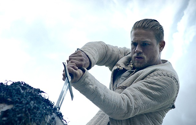 """Arthur (Charlie Hunnam) grips on to Excalibur to begin his destiny in """"King Arthur: Legend of the Sword."""" The movie is a retelling of the story of the fabled king of England."""